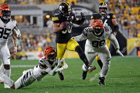 Pittsburgh Steelers running back James Conner (30) is tackled by Cincinnati Bengals free safety Jessie Bates (30) during the second half of an NFL football game in Pittsburgh