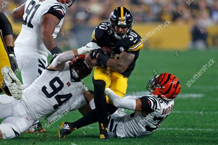 Stock Photo of Pittsburgh Steelers running back James Conner (30) is tackled by Cincinnati Bengals defensive end Sam Hubbard (94) and free safety Jessie Bates (30) during the first half of an NFL football game in Pittsburgh