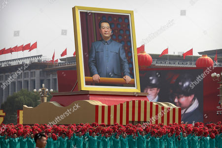 Stock Image of Participants wave floral bouquets as they march next to a large portrait of Chinese leader Hu Jintao during a parade commemorating the 70th anniversary of the founding of Communist China in Beijing, . Trucks carrying weapons including a nuclear-armed missile designed to evade U.S. defenses rumbled through Beijing as the Communist Party celebrated its 70th anniversary in power with a parade Tuesday that showcased China's ambition as a rising global force