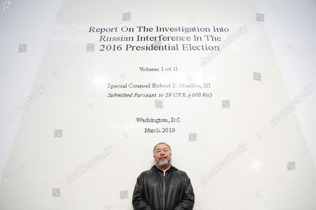 Ai WeiWei. Chinese artist Ai Weiwei poses for the media in front of his work made of Lego bricks of the front page of the Mueller report into Russian Interference in the 2016 US Presidential Election, at an art gallery in London, . This exhibition also features a new series of monumental sculptural work in iron, cast from giant tree roots sourced in Brazil