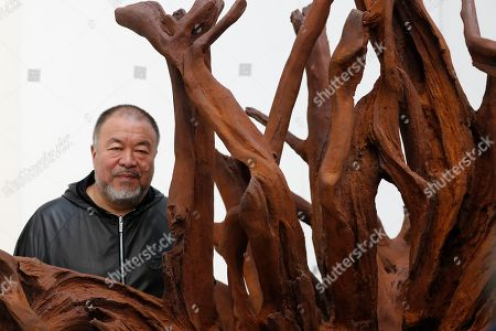 Ai WeiWei. Chinese artist Ai Weiwei poses for the media in front of his work cast iron work entitled 'Martin 2019' at an art gallery in London, . This exhibition features a new series of monumental sculptural work in iron, cast from giant tree roots sourced in Brazil