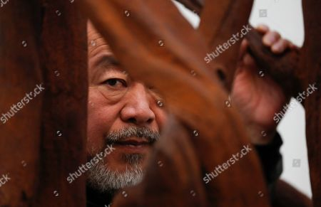 Ai WeiWei. Chinese artist Ai Weiwei poses for the media with cast iron work entitled 'Martin 2019' at an art gallery in London, . This exhibition features a new series of monumental sculptural work in iron, cast from giant tree roots sourced in Brazil