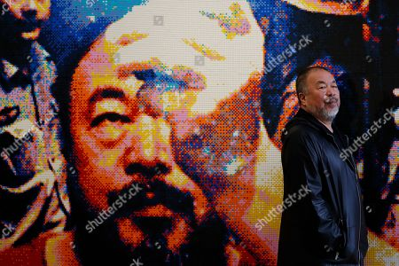 Ai WeiWei. Chinese artist Ai Weiwei poses for the media in front of his work in Lego bricks entitled 'Illumination 2019', at an art gallery in London, . This exhibition also features a new series of monumental sculptural work in iron, cast from giant tree roots sourced in Brazil