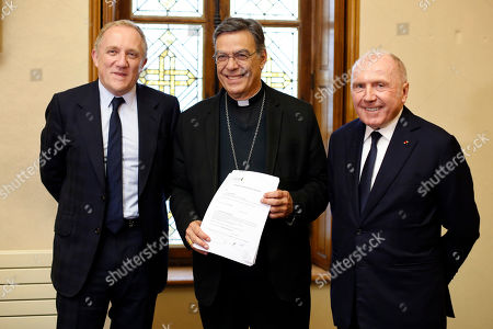 Francois-Henri Pinault, CEO of French luxury group Kering, left, his father Francois Pinault, right, and Archbishop of Paris Michel Aupetit, center, pose after signing an agreement to raise money for the rebuild of Notre-Dame cathedral, in Paris, . French billionaire Francois Pinault and his son Francois-Henri Pinault have made a 100 million euros ($109 million) donation for the rebuilding of Notre Dame Cathedral