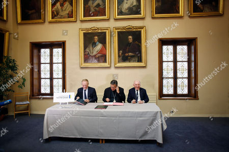Francois-Henri Pinault, CEO of French luxury group Kering, left, his father Francois Pinault, right, and Archbishop of Paris Michel Aupetit, center, sign an agreement to raise money for the rebuild of Notre-Dame cathedral, in Paris, . French billionaire Francois Pinault and his son Francois-Henri Pinault have made a 100 million euros ($109 million) donation for the rebuilding of Notre Dame Cathedral