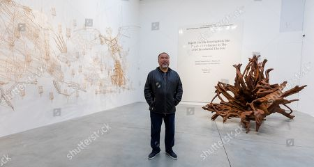 Chinese artist Ai Weiwei poses in front of his 'Martin 2019' Roots sculpture and his work of the front page of the Mueller report into Russian Interference in the 2016 US Presidential Election during a press preview at the Lisson Gallery, in London, Britain, 01 October 2019. The exhibition runs from 02 October to 02 November 2019 and features a new series of monumental sculptural work in iron cast from giant tree roots sourced in Brazil.