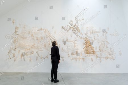 A woman looks at 'All Fingers Must Point Down 2015' by Chinese artist Ai Weiwei during a press preview at the Lisson Gallery, in London, Britain, 01 October 2019. The exhibition runs from 02 October to 02 November 2019 and features a new series of monumental sculptural work in iron cast from giant tree roots sourced in Brazil.