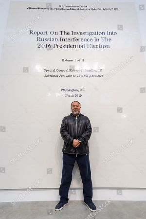 Chinese artist Ai Weiwei poses in front of his work of the front page of the Mueller report into Russian Interference in the 2016 US Presidential Election during a press preview at the Lisson Gallery, in London, Britain, 01 October 2019. The exhibition runs from 02 October to 02 November 2019 and features a new series of monumental sculptural work in iron cast from giant tree roots sourced in Brazil.