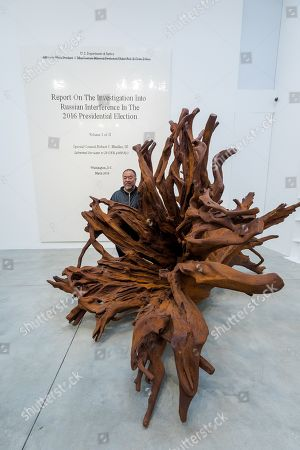 Chinese artist Ai Weiwei poses behind his 'Martin 2019' Roots sculpture and in front of his work of the front page of the Mueller report into Russian Interference in the 2016 US Presidential Election during a press preview at the Lisson Gallery, in London, Britain, 01 October 2019. The exhibition runs from 02 October to 02 November 2019 and features a new series of monumental sculptural work in iron cast from giant tree roots sourced in Brazil.