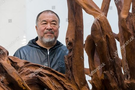 Stock Picture of Chinese artist Ai Weiwei poses behind of his 'Martin 2019' Roots sculpture during a press preview at the Lisson Gallery, in London, Britain, 01 October 2019. The exhibition runs from 02 October to 02 November 2019 and features a new series of monumental sculptural work in iron cast from giant tree roots sourced in Brazil.