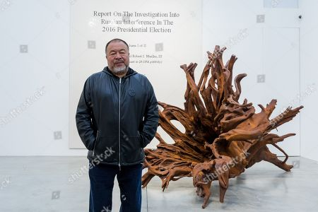 Stock Image of Chinese artist Ai Weiwei poses in front of his 'Martin 2019' Roots sculpture and his work of the front page of the Mueller report into Russian Interference in the 2016 US Presidential Election during a press preview at the Lisson Gallery, in London, Britain, 01 October 2019. The exhibition runs from 02 October to 02 November 2019 and features a new series of monumental sculptural work in iron cast from giant tree roots sourced in Brazil.