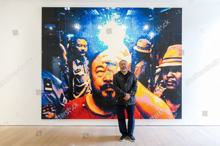Stock Photo of Chinese artist Ai Weiwei poses in front of his artwork 'Illumination 2019' made from Lego during a press preview at the Lisson Gallery, in London, Britain, 01 October 2019. The exhibition runs from 02 October to 02 November 2019 and features a new series of monumental sculptural work in iron cast from giant tree roots sourced in Brazil.