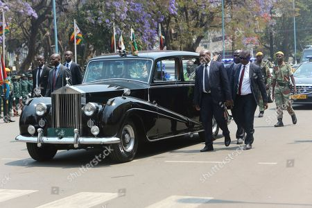 Bodyguards surround the car carrying Zimbabwe President Emmerson Mnangagwa at the opening session of parliament in Harare, Tuesday, Oct, 1, 2019. Zimbabwe's opposition lawmakers have walked out of Parliament as President Emmerson Mnangagwa presented his state of the nation address, a sign of the political tensions still gripping the country