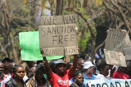 A supporter of Zimbabwean President Emmerson Mnangagwa holds up a banner in Harare, Tuesday, Oct, 1, 2019. Zimbabwe's opposition lawmakers have walked out of Parliament as President Emmerson Mnangagwa presented his state of the nation address, a sign of the political tensions still gripping the country