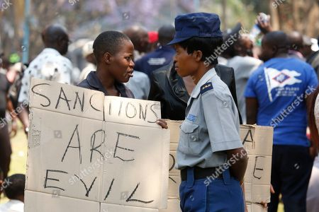 A ruling Zimbabwe African National Union Patriotic Front (Zanu PF) supporter holds a placard calling for the lifting of sanctions   outside the House of Parliament in Harare, Zimbabwe, 01 October 2019. Zimbabwean President Mnangagwa has officially opened the second session of the Ninth Parliament of Zimbabwe and addressed parliamentarians on the state of the nation.