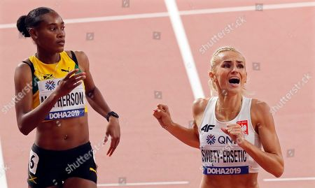 Stock Photo of Stephenie Ann McPherson (L) of Jamaica and Justyna Swiety-Ersetic (R) of Poland react after competing in the women's 400m semi finals at the IAAF World Athletics Championships 2019 at the Khalifa Stadium in Doha, Qatar, 01 October 2019.