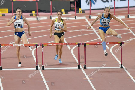 Jessica Turner, of Great Britain, Carolina Krafzik, of Germany, and Vera Rudakova, of participates as a neutral athlete, compete in the women's 400 meter hurdle heats at the World Athletics Championships in Doha, Qatar