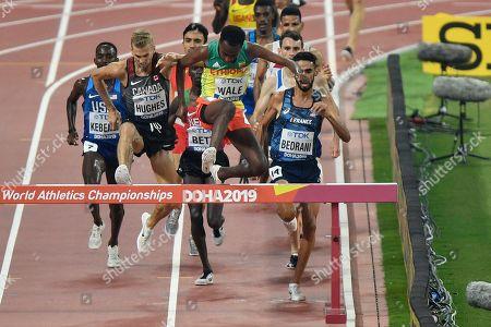 Getnet Wale, of Ethiopia, jumps as Djilali Bedrani, of France, right, Matthew Hughes, of Canada, second left, and Leonard Kipkemoi Bett, of Kenya, half hidden behind Wale, compete in the men's 3000 meter steeplechase heats at the World Athletics Championships in Doha, Qatar