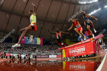 Getnet Wale, of Ethiopia, left, competes in a men's 3000 meter steeplechase heat at the World Athletics Championships in Doha, Qatar