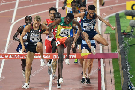 Getnet Wale, of Ethiopia, jumps with Djilali Bedrani, of France, right, and Matthew Hughes, of Canada, left, in the men's 3000 meter steeplechase heats at the World Athletics Championships in Doha, Qatar