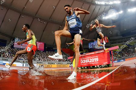 Getnet Wale, left, of Ethiopia; Djilali Bedrani, center, of France; and Matthew Hughes, right, of Canada; compete in a men's 3000 meter steeplechase heat at the World Athletics Championships in Doha, Qatar