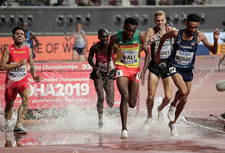 Stock Photo of Djilali Bedrani, of France, right, and Getnet Wale, of Ethiopia, center right, clear the water jump in the men's 3000 meter steeplechase heats at the World Athletics Championships in Doha, Qatar