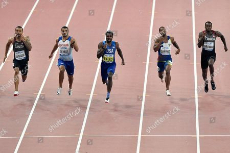 Noah Lyles of the U.S., center, on his way to win the gold medal in the men's 200 meter final ahead of Andre de Grasse of Canada, left, Adam Gemili of Great Britain, second left, Alex Quinonez of Ecuador, second right, and Aaron Brown of Canada, right, at the World Athletics Championships in Doha, Qatar