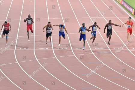 Noah Lyles of the U.S., fourth from right, crosses the finish line to win the gold medal in the men's 200 meter final ahead of others, from left, Ramil Guliyev of Turkey, Kyle Greaux of Trinidad and Tobago Andre de Grasse of Canada, Adam Gemili of Great Britain, Alex Quinonez of Ecuador, Aaron Brown of Canada, and Xie Zhenye of China, at the World Athletics Championships in Doha, Qatar