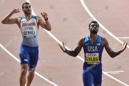 Noah Lyles of the U.S., right, celebrates winning the gold medal in the men's 200 meter final ahead of Adam Gemili of Great Britain, left, at the World Athletics Championships in Doha, Qatar