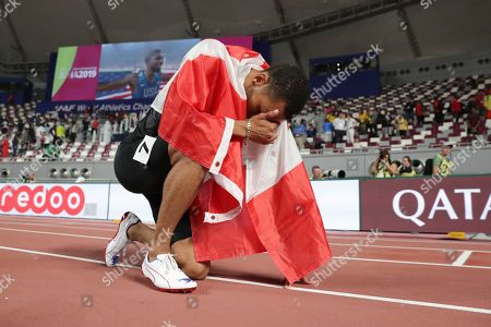 Andre de Grasse, of Canada, kneels on the track after winning the silver medal in the men's 200 meters at the World Athletics Championships in Doha, Qatar