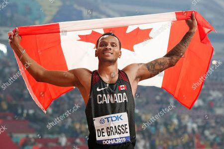 Andre de Grasse, of Canada, celebrates after winning the silver medal in the men's 200 meters at the World Athletics Championships in Doha, Qatar