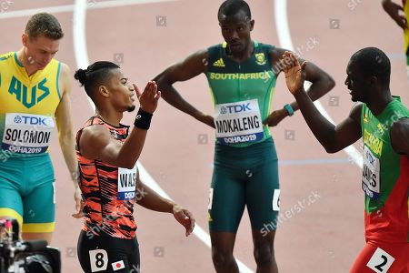 Julian Jrummi Walsh, of Japan, second left, celebrates with Kirani James, of Grenada, right, after competing in the men's 400 meter heats at the World Athletics Championships in Doha, Qatar