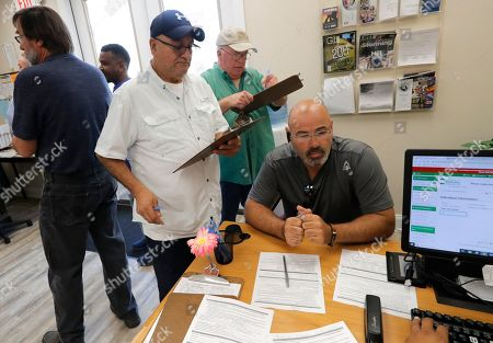 Laid off workers line up for job searches at a temporary office of the Louisiana Employment Commission, after the Bayou Steel Group mill shut down yesterday in LaPlace, La., . The Louisiana steel mill unexpectedly laid off hundreds of employees and says the factory will shut down in November