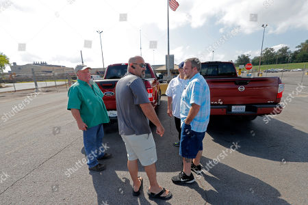 Laid off workers stand outside the closed Bayou Steel Group factory after turning in their uniforms in LaPlace, La., . The Louisiana steel mill unexpectedly laid off 376 employees and says the factory will shut down in November