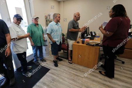 Laid off workers line up for job searches at a temporary office of the Louisiana Employment Commission, after the Bayou Steel Group mill shut down yesterday in LaPlace, La., . The Louisiana steel mill unexpectedly laid off 376 employees and says the factory will shut down in November