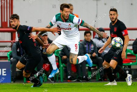 Lokomotiv's Fyodor Smolov, left, fights for the ball with Atletico Madrid's Felipe during the Champions League Group D soccer match between Lokomotiv Moscow and Atletico Madrid at the Lokomotiv Stadium in Moscow, Russia
