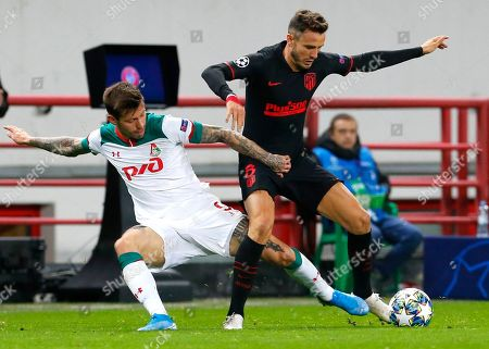 Lokomotiv's Fyodor Smolov, left, fights for the ball with Atletico Madrid's Saul during the Champions League Group D soccer match between Lokomotiv Moscow and Atletico Madrid at the Lokomotiv Stadium in Moscow, Russia
