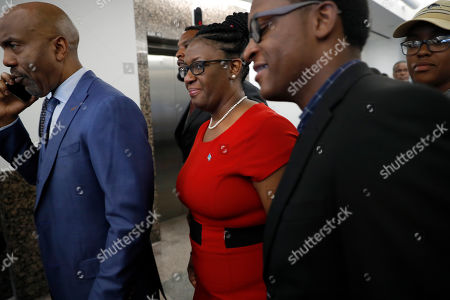 Stock Photo of Attorney Daryl Washington, left, Allison Jean, center, the mother of victim Botham Jean, and others arrive back at Frank Crowley Courts Building for the sentencing phase in the trial of fired Dallas police officer Amber Guyger, in Dallas. Guyger, who said she fatally shot her unarmed, black neighbor Botham Jean after mistaking his apartment for her own was found guilty of murder by a jury earlier on Tuesday