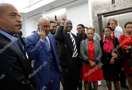 Stock Picture of Daryl Washington, Ben Crump. Attorneys Daryl Washington, on phone left, and Ben Crump, arm raised, and family and friends of Botham Jean arrive back at Frank Crowley Courts building for the sentencing phase in the trial of fired Dallas police officer Amber Guyger, in Dallas. Guyger, who said she fatally shot her unarmed, black neighbor Botham Jean after mistaking his apartment for her own was found guilty of murder by a jury earlier on Tuesday