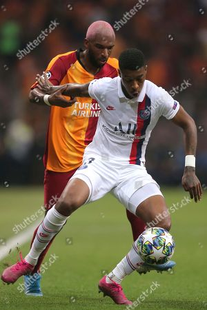 Galatasaray's Steven Nzonzi, left, and PSG's Presnel Kimpembe vie for the ball during the Champions League group A soccer match between Galatasaray and PSG in Istanbul