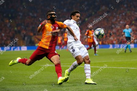 Galatasaray's Younes Belhanda, left, and PSG's Marquinhos vie for the ball during the Champions League group A soccer match between Galatasaray and PSG in Istanbul