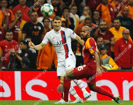 PSG's Thomas Meunier, left, shoots the ball in front of Galatasaray's Marcao, right, during a Champions League Group A soccer match between Galatasaray and PSG in Istanbul, . PSG won the match 1-0