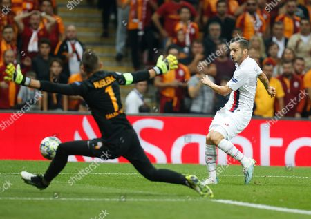 PSG's Pablo Sarabia, right, shoots the ball, as Galatasaray's goalkeeper and captain Fernando Muslera, left, tries to stop him, during a Champions League Group A soccer match between Galatasaray and PSG in Istanbul, . PSG won the match 1-0