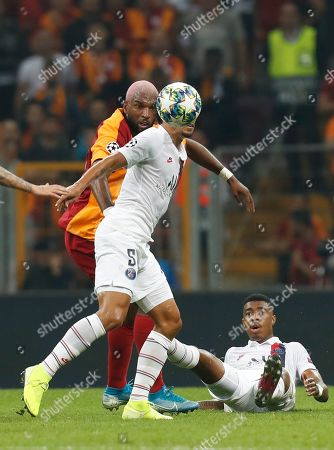 PSG's Marquinhos, centre, controls the ball as Galatasaray's Ryan Babel, left, tries to stop him during a Champions League Group A soccer match between Galatasaray and PSG in Istanbul, . PSG's Presnel Kimpembe, bottom right, looks on. gPSG won the match 1-0