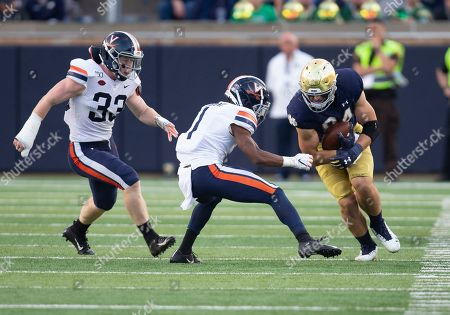 Notre Dame tight end Cole Kmet (84) runs with the ball after the catch as Virginia defensive back Nick Grant (1) pursues during NCAA football game action between the Virginia Cavaliers and the Notre Dame Fighting Irish at Notre Dame Stadium in South Bend, Indiana. Notre Dame defeated Virginia 35-20