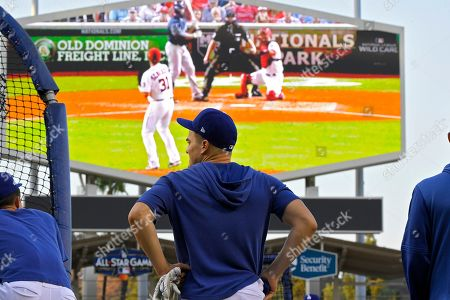 Los Angeles Dodgers' Enrique Hernandez waits to bat as the wildcard game between the Milwaukee Brewers and the Washington Nationals plays on the scoreboard during practice as they wait to find out who they will play in Game 1 of a National League division series baseball game, in Los Angeles