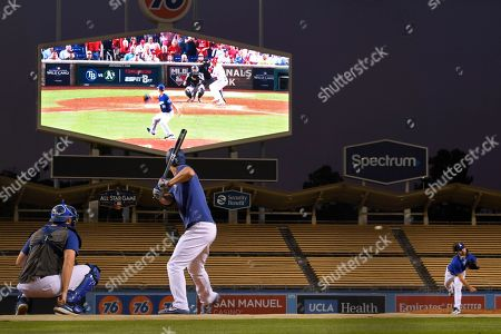 Stock Image of Tony Gonsolin, Corey Seager, Austin Barnes. Los Angeles Dodgers pitcher Tony Gonsolin, right, pitches to Corey Seager, as Austin Barnes catches during practice as they wait to find out who they will play in Game 1 of a National League division series baseball game, in Los Angeles