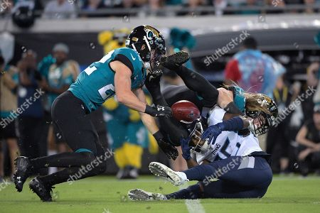 Tennessee Titans cornerback Adoree' Jackson (25) fumbles the football after getting hit by Jacksonville Jaguars defensive back Cody Davis (22) and defensive back Andrew Wingard (42) during the first half of an NFL football game, in Jacksonville, Fla