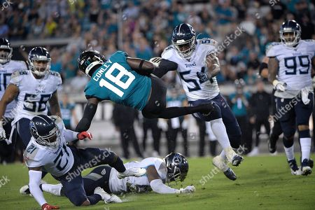 Jacksonville Jaguars wide receiver Chris Conley (18) is upended by Tennessee Titans cornerback Malcolm Butler (21) after catching a pass during the second half of an NFL football game, in Jacksonville, Fla