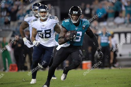 Jacksonville Jaguars wide receiver Chris Conley (18) runs after catching a pass in front of Tennessee Titans linebacker Harold Landry (58) during the second half of an NFL football game, in Jacksonville, Fla